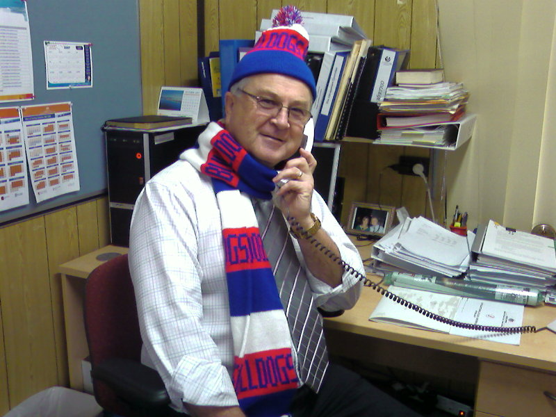 Jim in his office in his Doggies scarf and beanie.